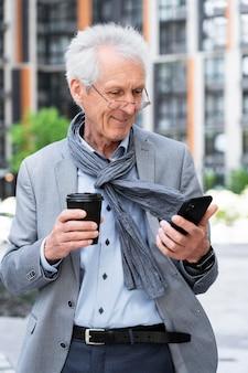 Stijlvolle oudere man in de stad die smartphone gebruikt terwijl hij koffie drinkt