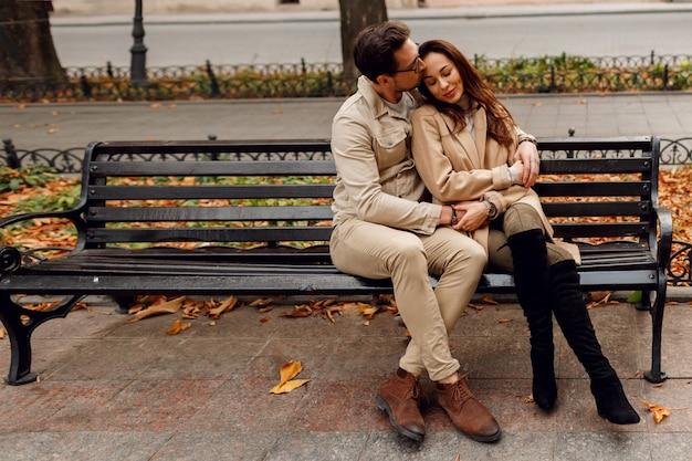 Stijlvolle paar verliefd poseren buiten. herfst modetrends. brunette model met stijlvolle man in beige jas zittend op de bank.