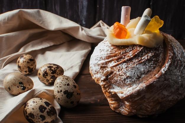 Stijlvolle paascake met marshmallows en geleiberen op een donkere rustieke houten achtergrond.