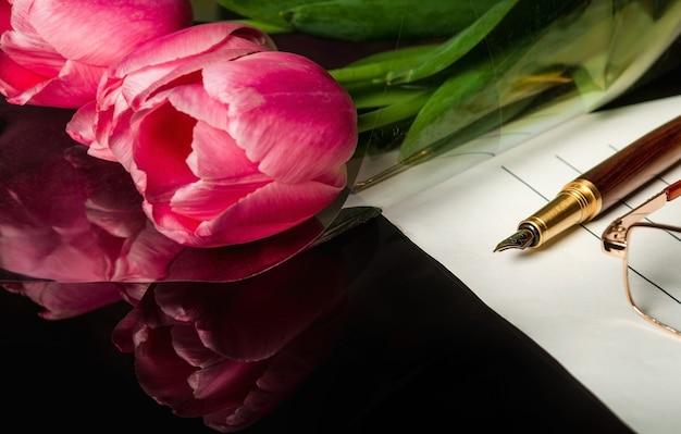 Stijlvolle pen op een blanco vel papier en bloemen in doorzichtige verpakking op de achtergrond.