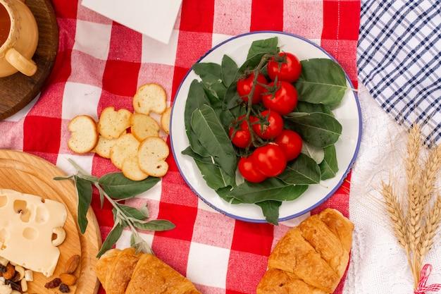 Stijlvolle picknick. verse croissants en tomaat op een sprei