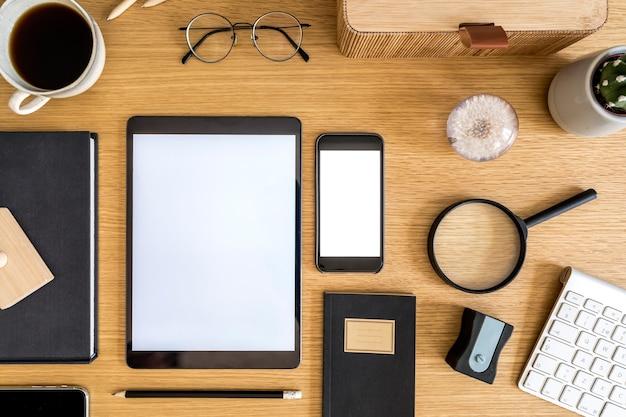 Stijlvolle platliggende zakelijke compositie op het houten bureau met tablet, cactussen, notities, fotocamera en kantoorbenodigdheden in modern concept van thuiskantoor.