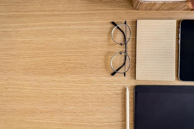 Stijlvolle platte zakelijke compositie op het houten bureau met glazen, notities, pen, kopieerruimte en kantoorbenodigdheden in modern concept.
