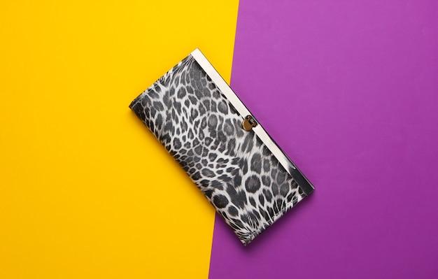 Stijlvolle portemonnee op een paarsgeel. modieus minimalisme.