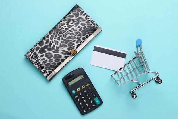 Stijlvolle portemonnee, winkelwagentje met bankpas en rekenmachine op blauw.