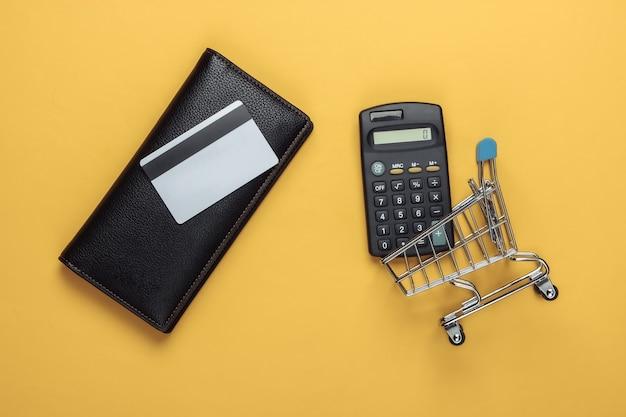 Stijlvolle portemonnee, winkelwagentje met bankpas en rekenmachine op geel.