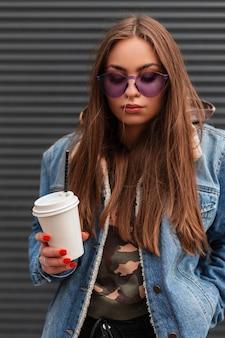 Stijlvolle portret hipster mooie jonge vrouw in modieuze paarse bril in een trendy blauw spijkerjasje met een warme drank in handen in de buurt van grijze muur op straat. aantrekkelijk meisjesmodel dat in openlucht rust.