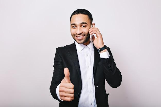 Stijlvolle portret jonge knappe man in wit overhemd, zwarte jas glimlachen, praten over de telefoon. succes, geweldig werk, ontmoeting, glimlachen, echte positieve emoties uiten.