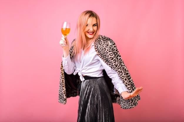 Stijlvolle positieve mooie jonge vrouw met plezier, het dragen van sprankelende cocktailoutfit in de avond en trendy bontjas met luipaardprint, roze achtergrond, genietend van wintervakantie feest.