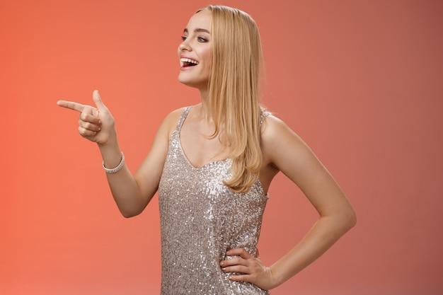 Stijlvolle prachtige jonge blonde kaukasische vriendin in zilveren stijlvolle avondjurk draaien profiel links wijzend nieuwsgierig glimlachend breed genieten van concertprestaties tijdens feest, rode achtergrond.