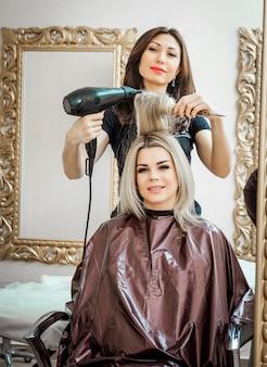 Stijlvolle professionele, kapper doet kapsel aan de klant met een föhn