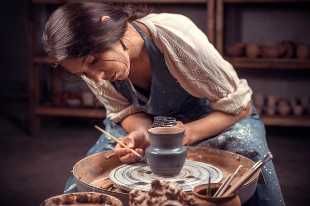Stijlvolle professionele pottenbakker die keramisch aardewerk maakt op wiel