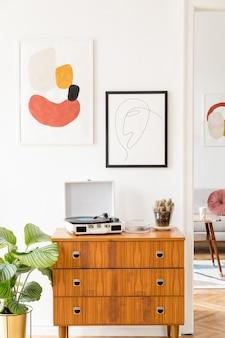Stijlvolle retro woonkamer met vintage commode, posterlijsten, planten, decoratie en elegante persoonlijke accessoires
