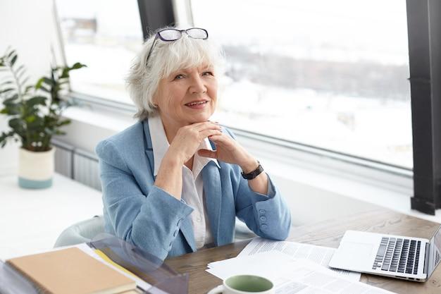 Stijlvolle, rijpe schrijfster van middelbare leeftijd met grijs haar en rimpels die vrolijk kijken en glimlachen, handen in elkaar grijpen, in een goed humeur zijn, zich geïnspireerd voelen terwijl ze aan haar nieuwe boek werkt