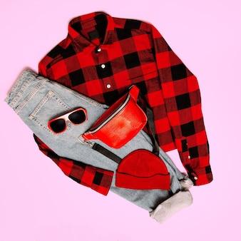 Stijlvolle rode accessoires clutch, pet, zonnebril en geruit hipstershirt. rock casual mode