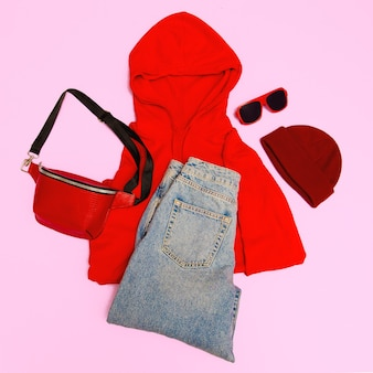 Stijlvolle rode accessoires clutch, pet, zonnebril en rode hoodie. straat casual mode