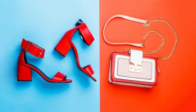Stijlvolle rode dames lederen sandalen schoenen vrouw tas sandalen op rode en blauwe achtergrond isolatie
