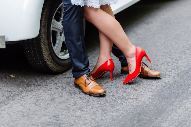 Stijlvolle rode en bruine schoenen van bruid en bruidegom in de buurt van de auto