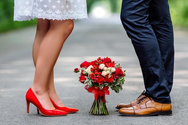 Stijlvolle rode en bruine schoenen van bruid en bruidegom met boeket rozen