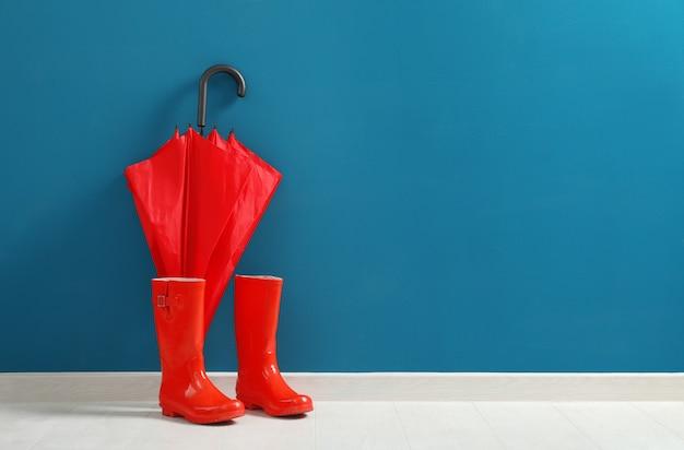 Stijlvolle rode paraplu en rubberen laarzen blauwe muur