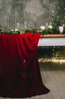 Stijlvolle rode tafel instelling met brandende kaarsen en kerstversiering op een grijze ondergrond