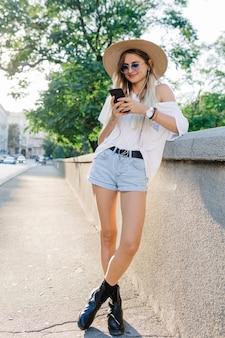 Stijlvolle romantische gelukkige vrouw is poseren op zonovergoten straat. het mooie meisje luistert muziek in hoofdtelefoons.