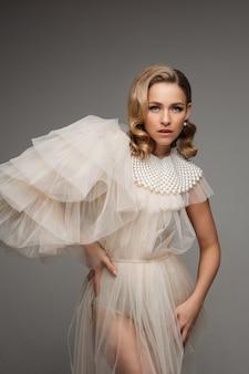 Stijlvolle romantische jonge mooie vrouw in jurk met parels kraag en perfecte kapsel poseren op grijze studio.