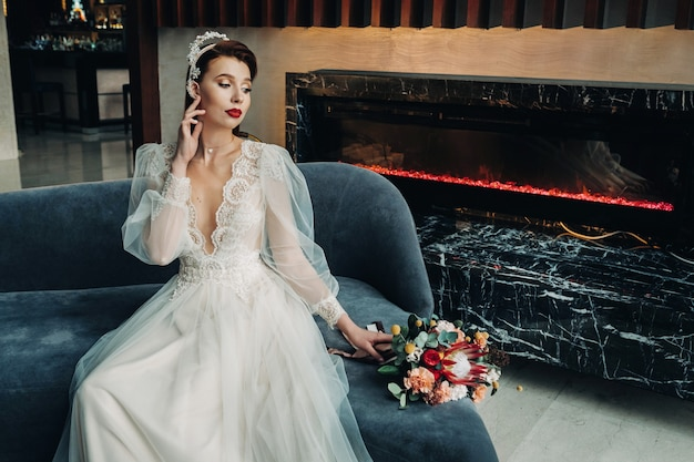 Stijlvolle roodharige bruid in een jurk met mouwen en een boeket in het interieur.