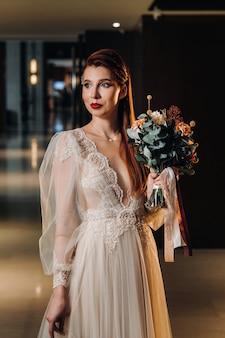 Stijlvolle roodharige bruid in een jurk met mouwen en een boeket in het interieur