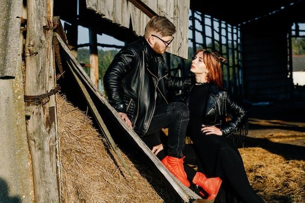 Stijlvolle roodharige meid en jongen poseren in lederen zwarte jassen