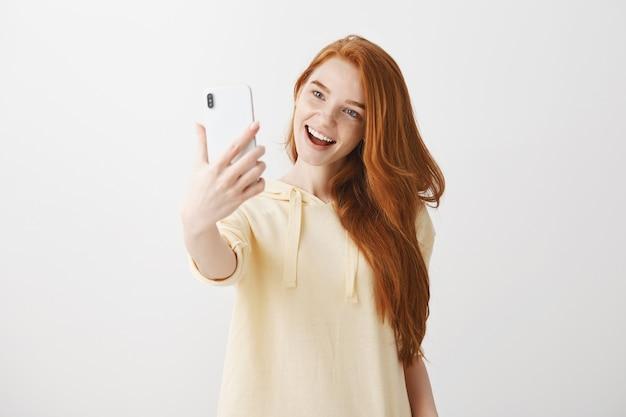 Stijlvolle roodharige meisje dat selfie met een tevreden glimlach neemt