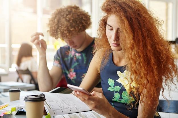 Stijlvolle roodharige vrouw die een bericht ontvangt van haar vriend tijdens haar studie in de coffeeshop