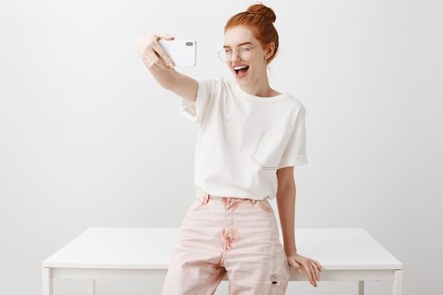 Stijlvolle roodharige vrouw selfie te nemen in kantoor