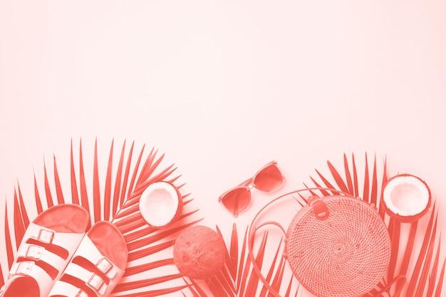 Stijlvolle rotan tas, kokosnoot, berkenstokken, palmtakken, zonnebrillen. bovenaanzicht achtergrond