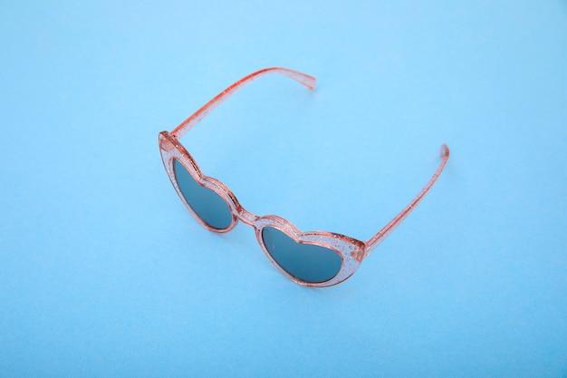 Stijlvolle roze zonnebril op pastelblauw. minimaal zomerconcept.