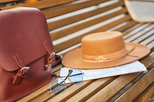 Stijlvolle rugzak met reizigersartikelen op houten bankje in de stad. ruimte kopiëren