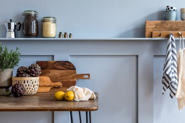 Stijlvolle samenstelling van keukeninterieur met houten familietafel, stoelen, groenten, kruiden, planten, fruit, voedselbenodigdheden en keukentoebehoren in grijs concept van huisdecor.