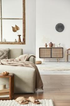 Stijlvolle samenstelling van woonkamer met design beige bank, houten kruk, commode, boek, decoratie, meubels, raam en elegante persoonlijke accessoires.