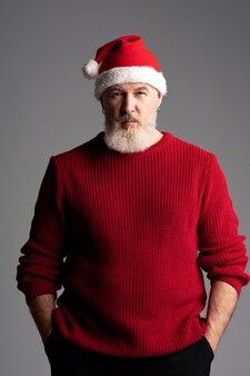 Stijlvolle santa man van middelbare leeftijd met baard met kerstmuts en rode trui kijken naar