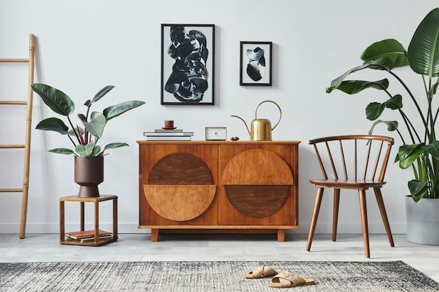 Stijlvolle scandinavische compositie van woonkamer met design commode, zwarte mock-up posterframes, stoel, houten kruk, boek, decoratie, planten en persoonlijke accessoires in modern interieur