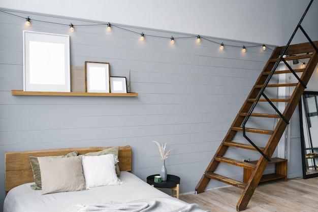 Stijlvolle scandinavische open ruimte met een bed en trap naar de tweede verdieping. een designkamer met grijze muren.