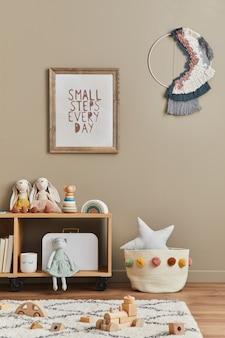 Stijlvolle scandinavische pasgeboren babykamer met bruin houten mock-up posterframe, speelgoed, pluche dieren- en kinderaccessoires