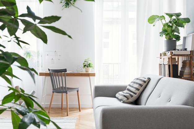 Stijlvolle scandinavische woonkamer met creatief houten bureau, grijze bank, bamboe boekenstandaard, boeken, planten en elegante decoraties in design woondecoratie