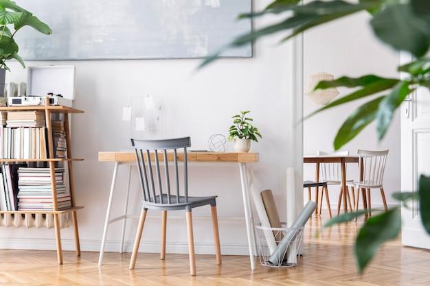 Stijlvolle scandinavische woonkamer met design meubelen, planten, bamboe boekenstandaard, houten bureau, kunstschilderijen, bruin parket in modern interieur