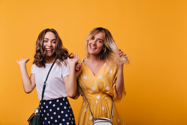 Stijlvolle schattige dames dansen en lachen in hun vrije tijd. geweldige vrouwelijke modellen die geluk uitdrukken terwijl ze poseren op oranje.