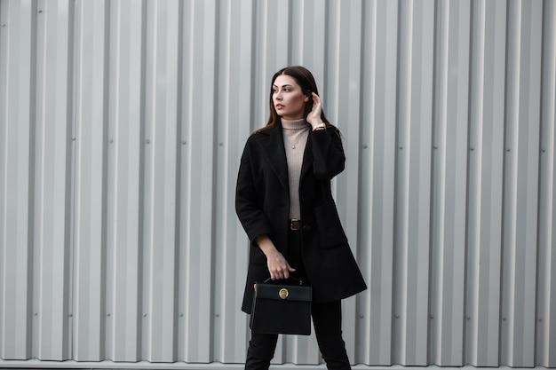 Stijlvolle schattige jonge vrouw met bruin lang haar in seizoensgebonden trendy zwarte jas met mode lederen tas poseren in de buurt van een zilveren metalen wand buitenshuis. bedrijfsmeisjesmodel in de stad. schoonheid modieuze dame.