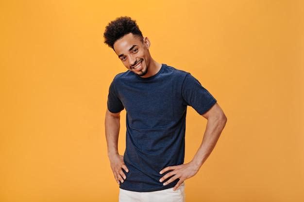 Stijlvolle schattige kerel glimlachend en kijkend naar camera op oranje muur