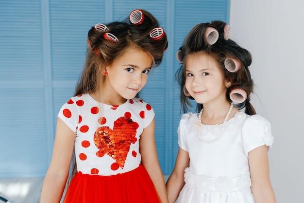 Stijlvolle schattige meisjes met krulspelden kijken elkaar binnen