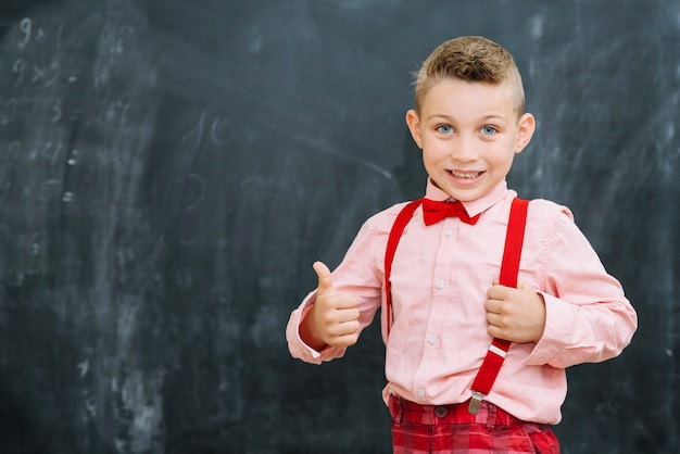 Stijlvolle schooljongen gesturing duimen omhoog