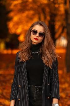 Stijlvolle schoonheidszakenvrouw met rode lippen in modieuze kleding met vintage zonnebril loopt in het park met gekleurd oranje blad